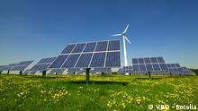 Solaranlage und Windrad auf grüner Wiese