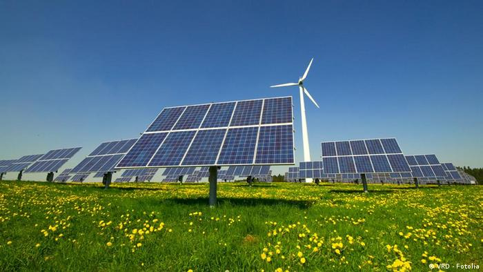 Solar panels and a wind turbine on a grassy field.