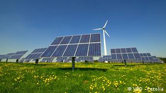 Solar panels and a turbine in a green meadow