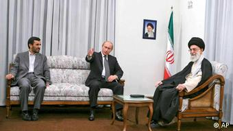 Under a picture of the Iranian late revolutionary founder Ayatollah Khomeini, Russian President Vladimir Putin, center, talks with Iranian supreme leader Ayatollah Ali Khamenei, right, as Iranian President Mahmoud Ahmadinejad listens during their meeting in Tehran, Iran, Tuesday, Oct. 16, 2007. Russian President Vladimir Putin refused to set a date Tuesday for the start-up of Iran's first nuclear power plant, but stressed that Moscow would not back out of its commitment to complete the project. (AP Photo/Mehr News Agency, Sajjad Safari)