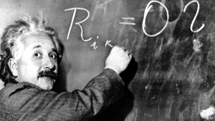 Albert Einstein writing on chalkboard