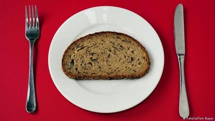 Scheibe Brot auf Teller mit Besteck