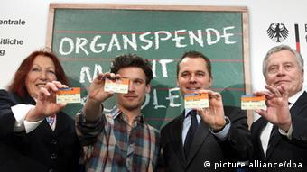Four people pose with their German organ donor ID cards (Photo: Wolfgang Kumm dpa/lbn +++(c) dpa - Bildfunk+++)