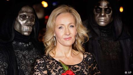 Joanne K. Rowling neben zwei Gestalten mit unheimlichen Masken (AP)