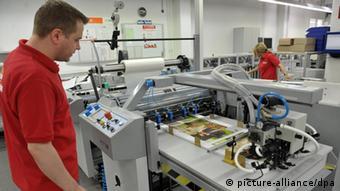 An employee at a color printer for a photo album. (Photo: Carmen Jaspersen dpa/lni)