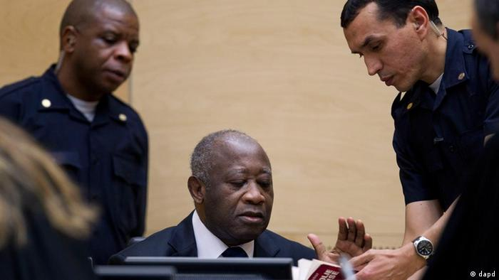 Former Ivory Coast President Laurent Gbagbo, center, and security guards at the International Criminal Court