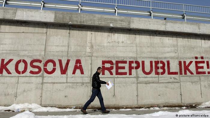 A pedestrian walks by a graffiti reading 'Kosova Republic!' in Kosovo's capital Pristina