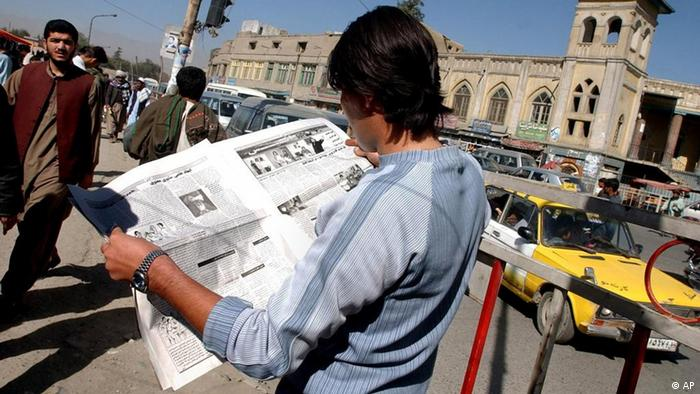 An Afghan youth browses the local newspaper Kabul Weekly. looking for an article about arrested journalist Ali Mohaqiq Nasab, in front of a mosque in Kabul, Afghanistan on Oct. 20, 2005 (AP Photo/Musadeq Sadeq)
