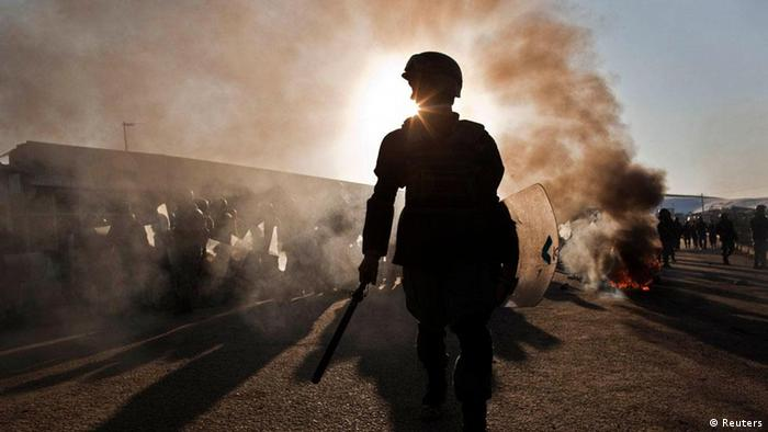 An anti-riot policeman looks for protesters during clashes with protesters