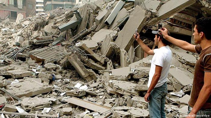 Lebanese citizens take pictures with mobile phones of debris in Haret Hreik district in southern Beirut after an Israeli missile attack in July 2006.