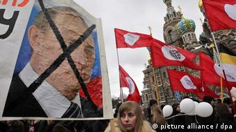Protesters hold up an anti-Putin placard