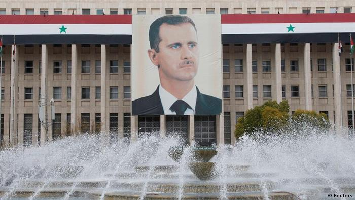 The picture of the Syria's President Bashar al-Assad is seen on central bank building in Damascus February 24, 2012. REUTERS/Khaled al-Hariri (SYRIA - Tags: POLITICS CIVIL UNREST)