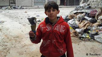 A boy holds the remain of a mortar in this handout picture taken by Syrian National Council (SNC) member Moulhem Al-Jundi in Karm Al Zaytoon, a neighbourhood of Homs, February 23, 2012. Picture taken February 23, 2012. REUTERS/Moulhem Al-Jundi/Handout (SYRIA - Tags: POLITICS CIVIL UNREST) FOR EDITORIAL USE ONLY. NOT FOR SALE FOR MARKETING OR ADVERTISING CAMPAIGNS. THIS IMAGE HAS BEEN SUPPLIED BY A THIRD PARTY. IT IS DISTRIBUTED, EXACTLY AS RECEIVED BY REUTERS, AS A SERVICE TO CLIENTS