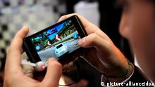 A man plays with the LG Optimus 3D mobile phone during the Mobile World Congress held in Barcelona, Catalonia, northeastern Spain, on 14 February 2011. The 2011 Mobile World Congress will be held 14-17 February. Around 50,000 senior mobile leaders from 20 countries participate in this edition. Photo: Toni Albir --
