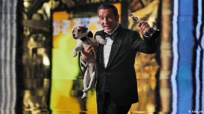 Best actor winner Jean Dujardin of France carries Uggie the dog after The Artist won the Oscar for Best Picture at the 84th Academy Awards in Hollywood, California, February 26, 2012. REUTERS/Gary Hershorn (UNITED STATES) (OSCARS-SHOW)