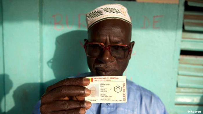 A man holds up his voting card during Senegal's presidential elections in the capital Dakar, February 26, 2012. Senegal's President Abdoulaye Wade faces re-election on Sunday, having defied opposition efforts to block him from standing and warnings that his candidacy risked destabilising the usually tranquil West African state. REUTERS/Joe Penney (SENEGAL - Tags: POLITICS ELECTIONS)