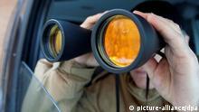 ILLUSTRATION - Ein Mann schaut am 27.12.2010 in einem Auto in Hannover durch ein Fernglas.