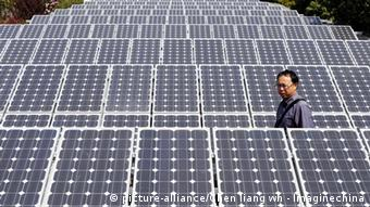 A man walks amid solar panels at a solar power facility in Wuhan, central China
