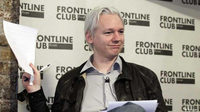 WikiLeaks founder Julian Assange holds a document containing leaked information at a news conference in London, February 27, 2012. The anti-secrecy group WikiLeaks began publishing on Monday more than five million emails from a U.S.-based global security analysis company that has been likened to a shadow CIA. REUTERS/Finbarr O'Reilly (BRITAIN - Tags: POLITICS MEDIA)