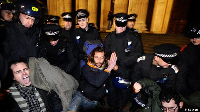 A man prays as riot police remove protesters from the Occupy encampment on the steps of St Paul's Cathedral in London February 28, 2012. Bailiffs began evicting British anti-capitalism activists from a protest camp outside St Paul's Cathedral in London in the early hours of Tuesday morning.