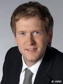 A young man (Professor Henning Vöpel) wearing a business suit smiles at the camera (Photo: Universität Wuppertal)