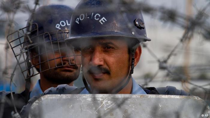 Pakistani police officers stand guard behind a barbed wire as they look towards protestors during an anti NATO rally in Islamabad, Pakistan on Thursday, Dec. 8, 2011.