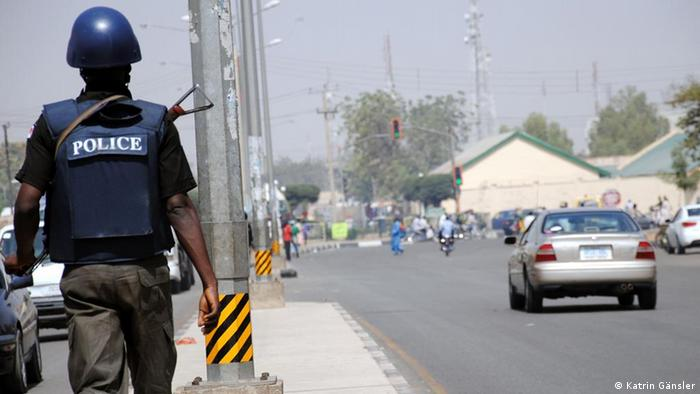 A police man and blocked off roads in Kano
