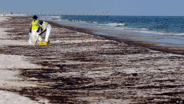 Crews work to clean up oil washed ashore at Pensacola Beach in Pensacola Fla., Wednesday, June 23, 2010. (ddp images/AP Photo/ Michael Spooneybarger)