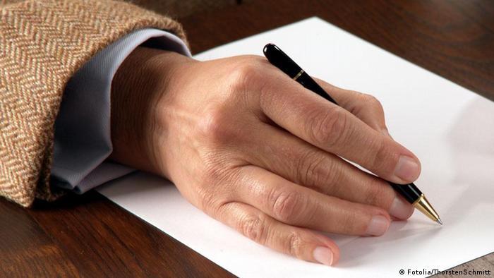 Mão com uma caneta sobre uma folha de papel