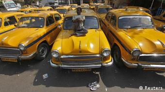 A driver rests on his yellow ambassador taxi during a country-wide strike in Kolkata