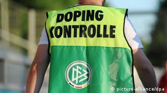 Ein Mann geht mit einer Weste mit der Aufschrift Doping Kontrolle an der Seitenlinie entlang. (Foto: Arne Dedert dpa)