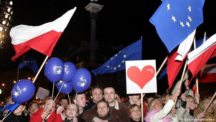 Menschen winken mit polnischen und Europafahnen bei den Feiern zum EU-Beitritt auf dem Zamkowy-Platz in Warschau. Feuerwerke, Konzerte und Volksfeste: In ganz Europa haben Millionen Menschen die Erweiterung der EU gefeiert. Fast 15 Jahre nach dem Fall der Berliner Mauer ist das einst zerrissene Europa wieder vereint. Die Europäische Union hat am 1.5. zehn neue Mitglieder zumeist aus Ost- und Mitteleuropa aufgenommen. Etwa 74 Millionen Bürger kommen hinzu. In der EU leben nun fast 455 Millionen Menschen. Ein Jahr nach dem Völkerfrühling hat ein pragmatischer Umgang mit dem EU-Alltag eingesetzt. (zu Korr: Gewelkter Lorbeer: EU-Alltag prägt das Beitritts-Jubiläum der Neuen vom 26.04.2005) +++(c) dpa - Bildfunk+++