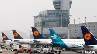 Aircrafts parked on apron in front of traffic control tower at Frankfurt's airport