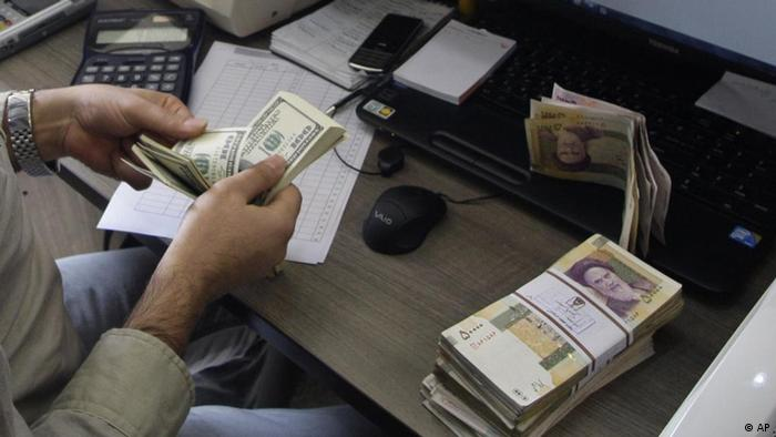 A currency exchange bureau worker counts US dollars, as Iranian bank notes are seen