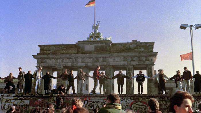 Berliners sing and dance atop the Berlin Wall to celebrate the opening of East-West German borders November 10, 1989 (Photo: AP/Thomas Kienzle)