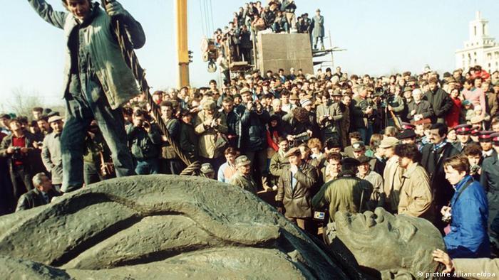 Eine Menschenmenge umringt im März 1990 in Bukarest eine umgestürzte Lenin-Statue (Foto: picture alliance/dpa)