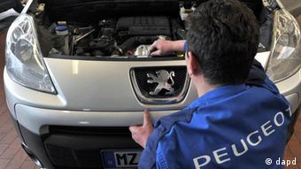 A mechanic works on a Peugeot car