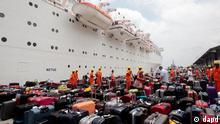 Passengers of the Costa Allegra cruise ship look for their baggage upon their arrival at Victoria's harbor, Seychelles Island, Thursday, March 1, 2012. A disabled cruise ship carrying more than 1,000 people docked in the island nation of the Seychelles Thursday after three days at sea without power since a fire broke out in the generator room on Monday. (Foto:Gregorio Borgia/AP/dapd)