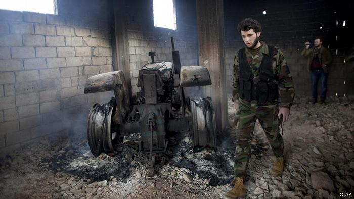 A Free Syrian Army soldier walks next to a burned tractor