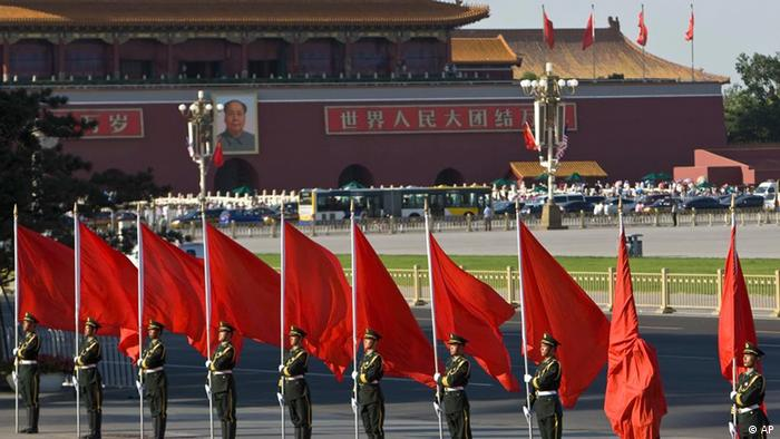 A member of an honor guard is wrapped in a red flag he holds during a welcome ceremony for the visiting Malaysian prime minister near the Tiananmen Square in Beijing Wednesday, June 3, 2009, on the eve of the 20th anniversary of the bloody crackdown on 1989 pro-democracy protests. (AP Photo/Alexander F. Yuan)