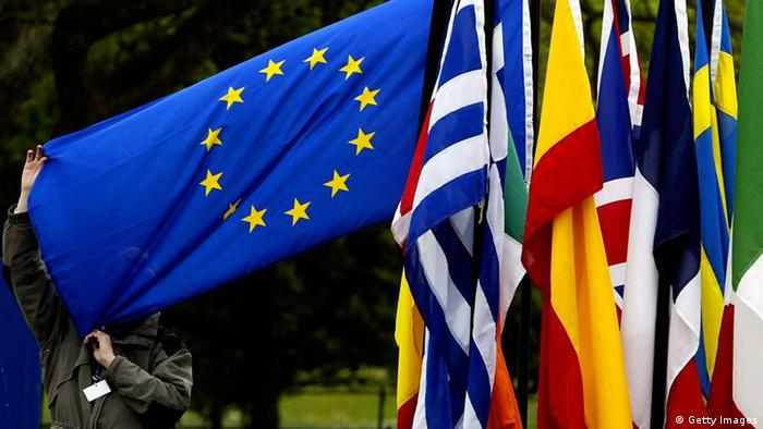 A man checks the flags of the European Union countries as they are gathered together ahead of the EU enlargement ceremony in 2004 Photo: Ian Waldie/Getty Images