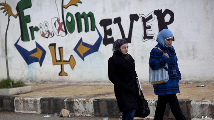 Women walk pass a graffiti that reads Freedom for Ever on the outskirts of Idlib, north Syria, Thursday, March 1, 2012. (Foto:Rodrigo Abd/AP/dapd)