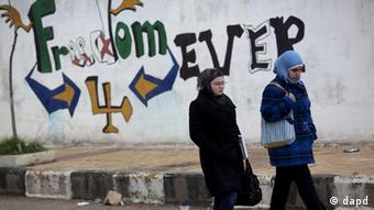 Women walk pass a graffiti that reads Freedom for Ever on the outskirts of Idlib, north Syria