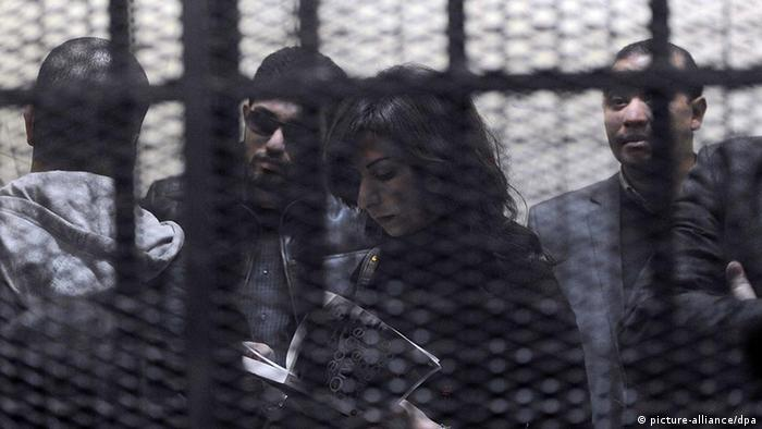 The defendants stand in a cage during the opening of their trial in Cairo (Photo: Mohamed Omar)