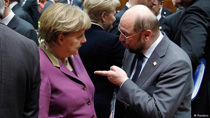 In a crowded room, a bald man in a business suit points a finger at Chancellor Merkel, who's wearing a purple business suit. (Photo: REUTERS/Francois Lenoir)