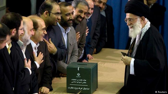 Iran's Supreme Leader Ayatollah Ali Khamenei greets election officials as he presents his identification papers to cast his ballot in the parliamentary election in Tehran March 2, 2012.