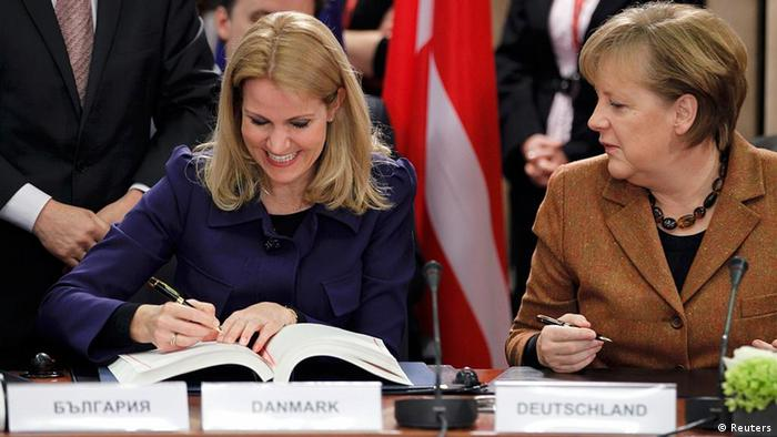Denmark's Prime Minister Helle Thorning Schmidt (L) and Germany's Chancellor Angela Merkel (R) sign a fiscal compact enshrining common debt rules among the 17 members of the euro zone during a European Union leaders summit in Brussels March 2, 2012 . REUTERS/Francois Lenoir (BELGIUM - Tags: POLITICS BUSINESS)