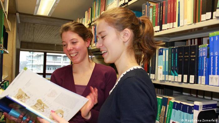 Das Foto zeigt die Schülerin Annika (re) und die Medizinstudentin Friedrike in der Bibiliothek der Ruhruniversität Bochum (RUB) zwischen den Bücherregalen in der medizinischen Abteilung.