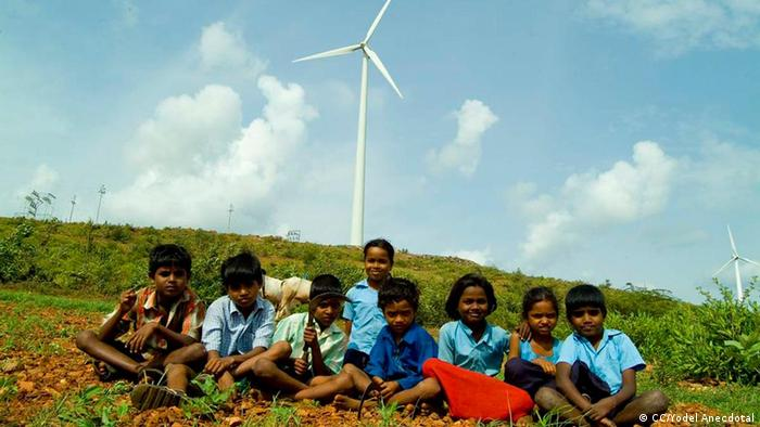 Indian children sit in a field with a windmill in the background