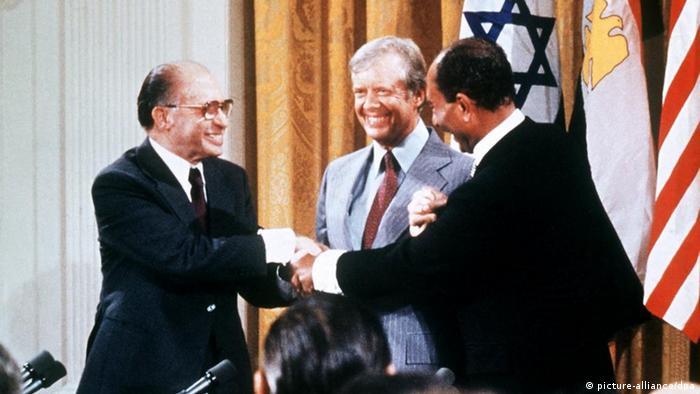 Anwar el Sadat und Menachem Begin reichen sich die Hände in der Mitte Jimmy Carter (picture-alliance/dpa)